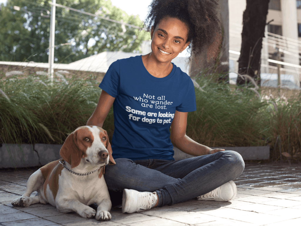 girl petting a beagle dog wearing a tshirt that says All who wander are not Lost. Some are looking for dogs to pet.