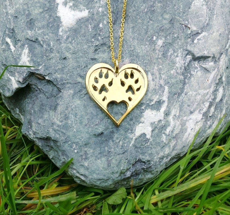 gold plated heart pendant with ferret paw prints on it